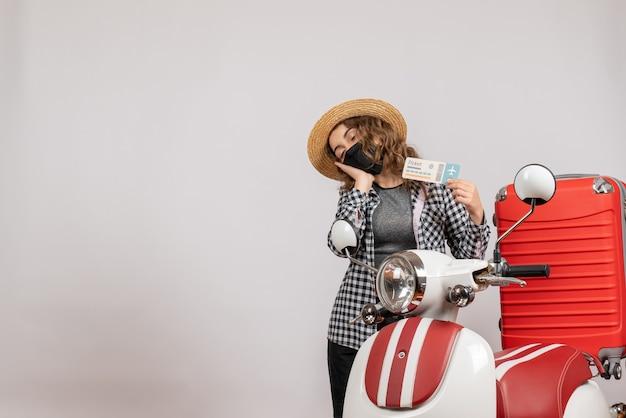 Niña soñolienta con máscara negra sosteniendo boleto de pie cerca de ciclomotor rojo