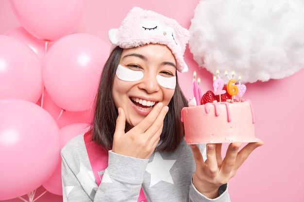 Niña sonríe ampliamente sostiene pastel festivo disfruta celebrando el 26 ° cumpleaños en casa se somete a tratamientos de belleza antes de que la fiesta use ropa de dormir antifaz
