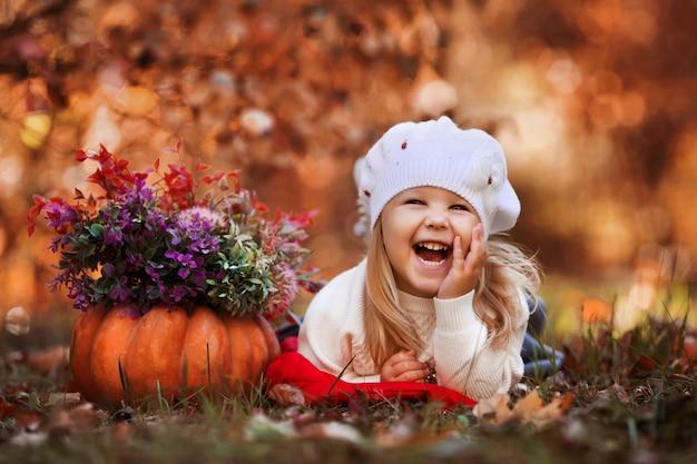 Niña sonríe y miente en las hojas de otoño