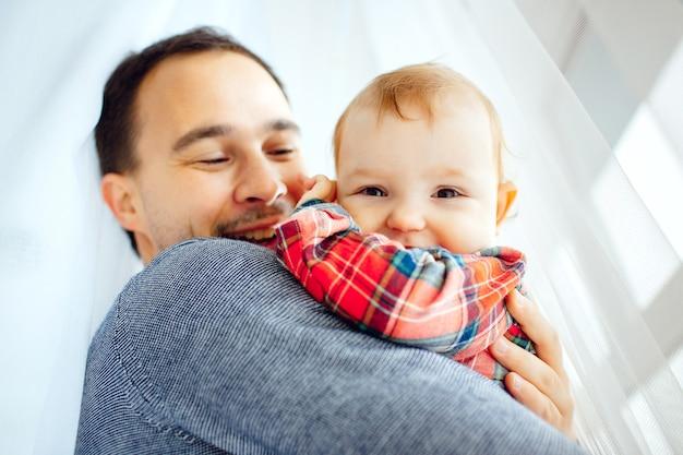 Niña sonríe sentada en los brazos del padre