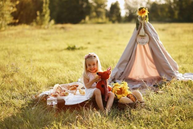 Niña sonríe y sostiene un peluche. picnic de verano