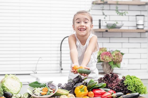 Una niña sonríe y sostiene verduras frescas en su mano mientras prepara una ensalada.