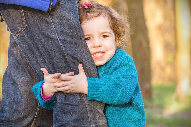 Niña sonriendo y abrazando la pierna de papá, familia