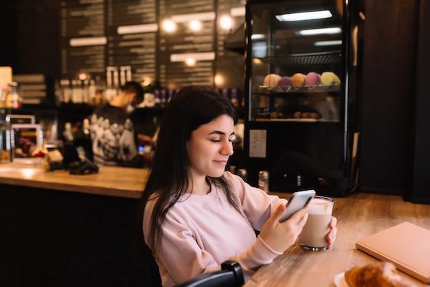 Niña sonriendo, bebe café en la cafetería y leyendo el teléfono.