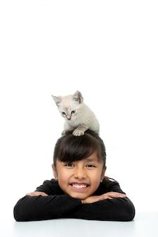 Niña sonriendo con gatito blanco vertical