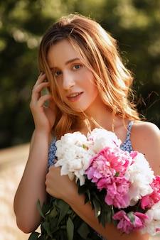 Niña sonriendo. imagen romántica para pasear por la ciudad. en sus manos hay flores.