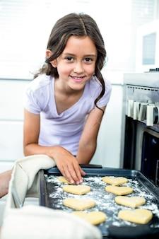 Niña sonriendo mientras toca las galletas en forma de corazón en la bandeja