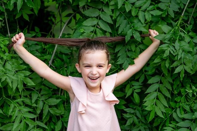Niña sonriente de 5 a 6 años se para en el parque junto a un árbol y sostiene su cabello, feliz infancia, día del niño