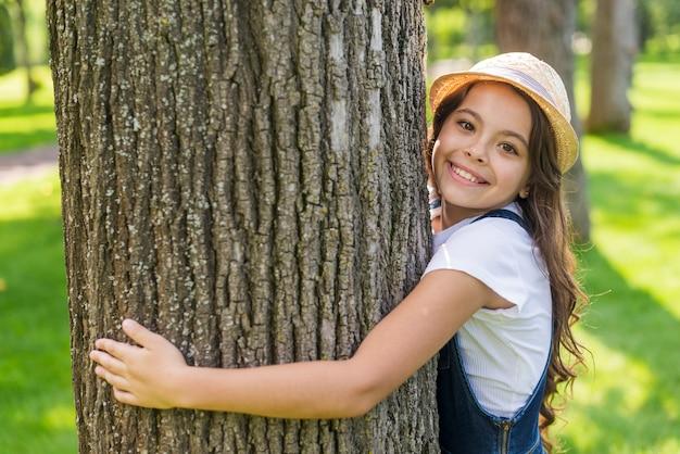 Niña sonriente abrazando un árbol