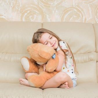 Niña sonriente abrazando a su oso de peluche sentado en el sofá