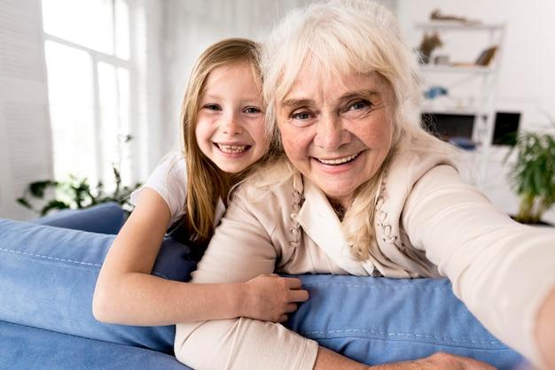 Niña sonriente y abuela en casa