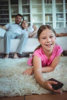 Niña sonriente acostada en la alfombra y cambiar canales