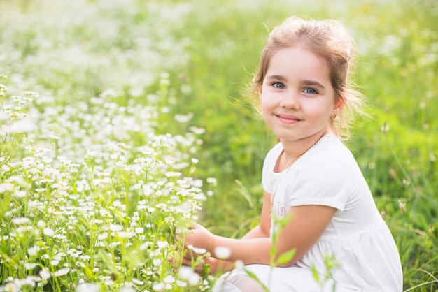 Niña sonriente agachándose cerca de la flor silvestre en el campo