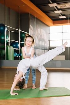 Niña sonriente ayudando a su hermana a hacer ejercicio en el gimnasio
