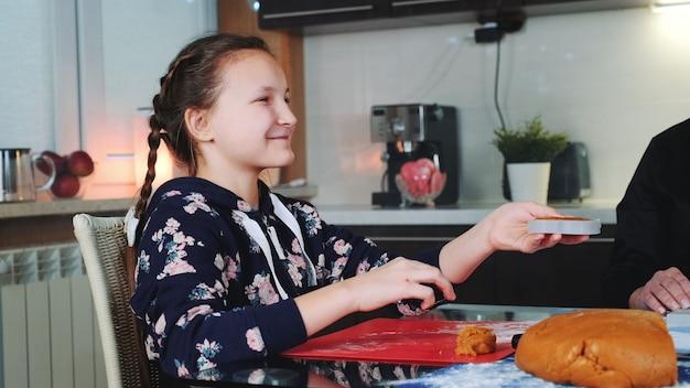 Niña sonriente ayudando a su madre a hacer galletas de jengibre