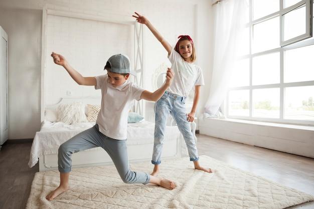 Niña sonriente bailando con su hermanito en casa