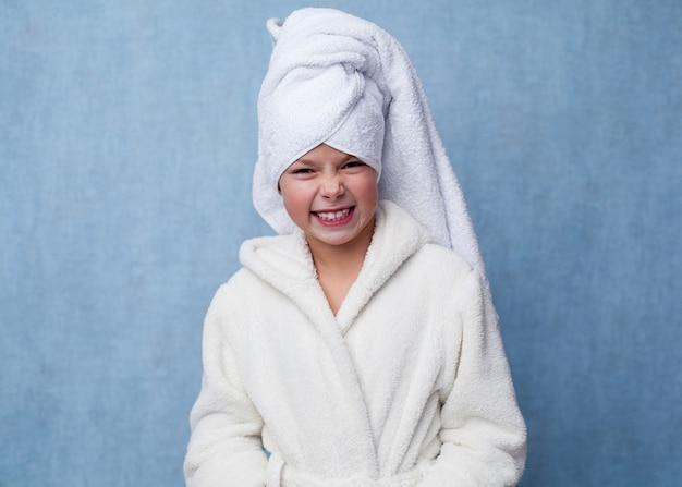 Niña sonriente en bata de baño blanca