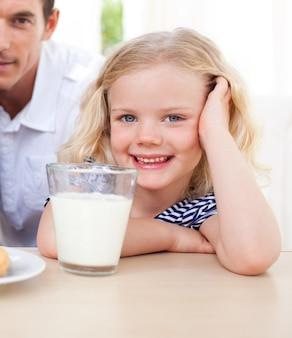 Niña sonriente bebiendo leche