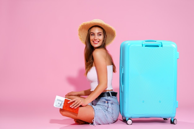 La niña sonriente con boletos va a viajar sentada cerca de la maleta en pantalones cortos y sombrero de paja pi ...