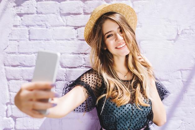 Niña sonriente con cabello brillante disfrutando del buen tiempo durante la caminata y haciendo selfie