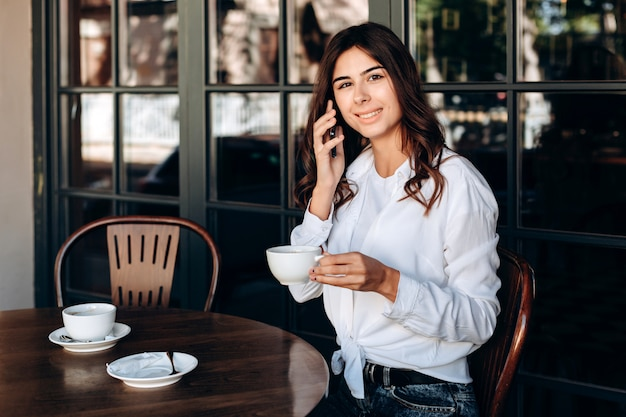 Niña sonriente en camisa blanca tiene taza y habla en café