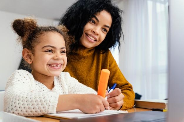 Niña sonriente en casa durante la escuela en línea con hermana mayor