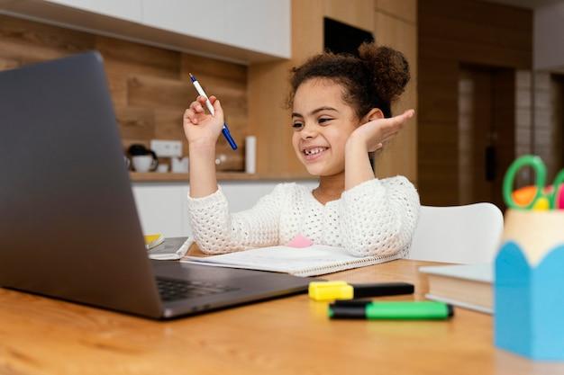 Niña sonriente en casa durante la escuela en línea