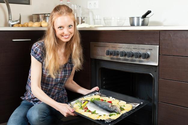 Niña sonriente cocinando pescado crudo en el horno