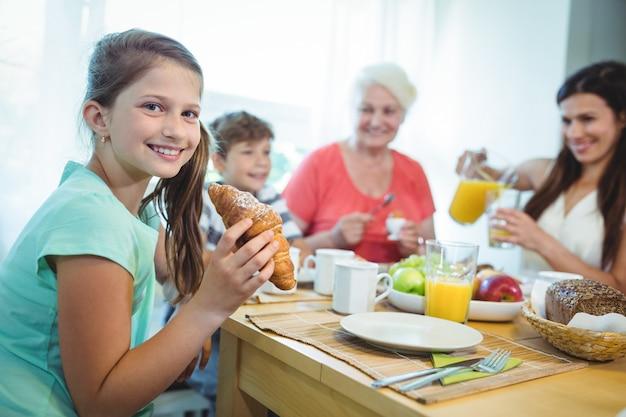 Niña sonriente comiendo un croissant mientras desayuna