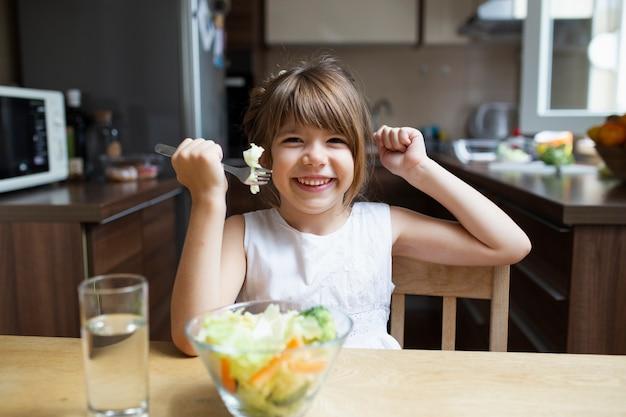 Niña sonriente comiendo ensalada con cubiertos