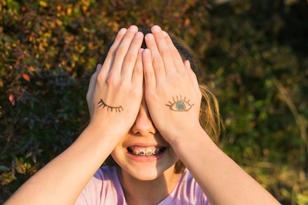 Niña sonriente cubriendo sus ojos con tatuajes en la palma