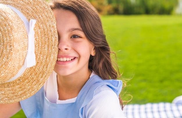 Niña sonriente cubriéndose los ojos con un sombrero de paja