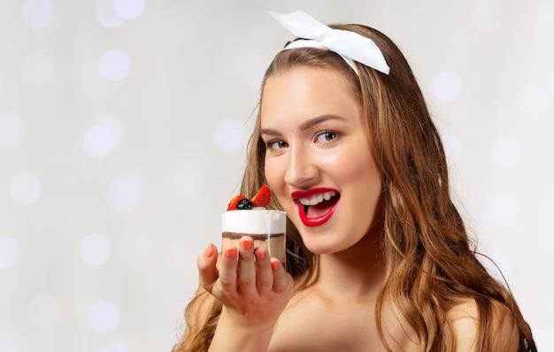 Niña sonriente con cupcake en mano