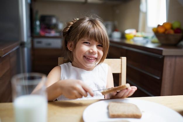Niña sonriente desayunando en casa