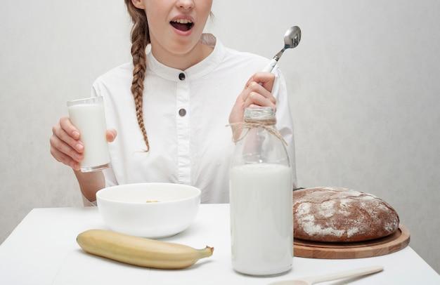 Niña sonriente desayunando con fondo blanco