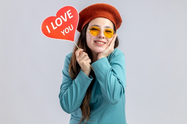 Niña sonriente en el día de san valentín con sombrero con gafas sosteniendo un corazón rojo en un palo con te amo texto poniendo la mano en la mejilla aislado sobre fondo blanco.