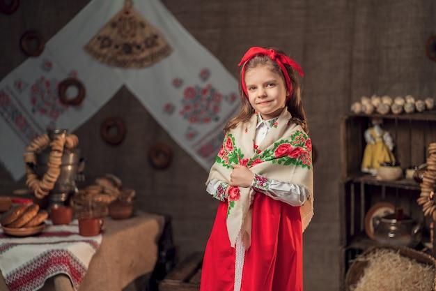 Niña sonriente con diadema roja y chal ornamental sonriendo a la cámara de pie junto a la mesa con fiesta de carnaval