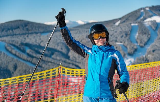 Niña sonriente disfrutando de vacaciones de esquí de pie en la montaña nevada