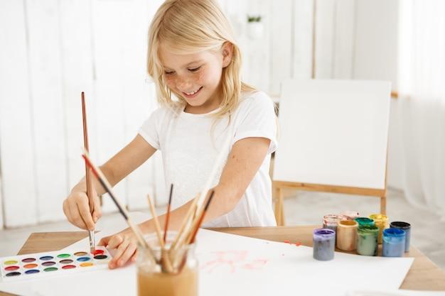 Niña sonriente e inspirada con cabello rubio y pecas peinando alegremente el pincel en pintura roja, con una nueva idea para una foto.