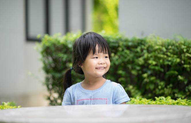 Niña sonriente en camisa azul, sentado en el parque