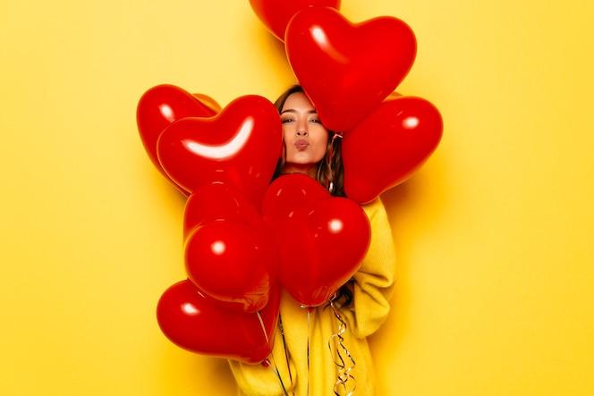 Niña sonriente en suéter amarillo dando un beso, mirando fuera de manojo de globos rojos.