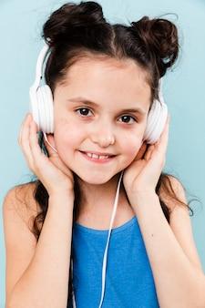 Niña sonriente escuchando música en los auriculares