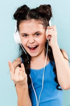 Niña sonriente escuchando música rock en los auriculares