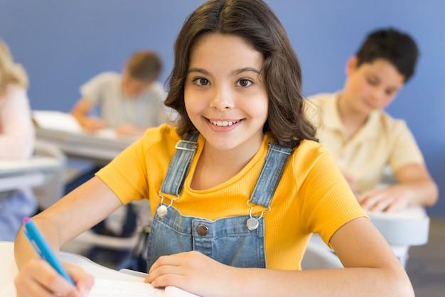 Niña sonriente en la escuela escribiendo