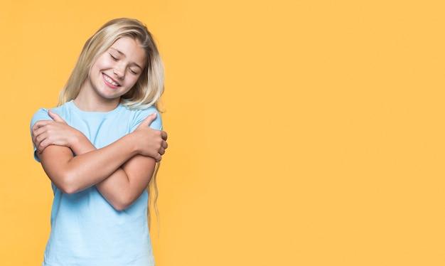 Niña sonriente de espacio de copia abrazándose a sí misma