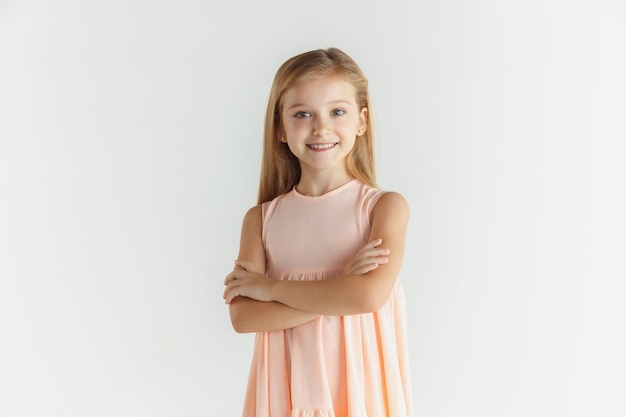 Niña sonriente con estilo posando en vestido aislado sobre fondo blanco de estudio. modelo de mujer rubia caucásica. emociones humanas, expresión facial, infancia. de pie con las manos cruzadas.