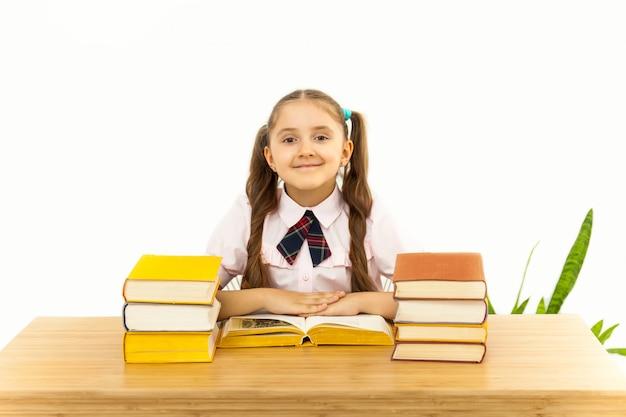 Niña sonriente estudiante con muchos libros en la escuela