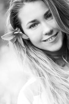 Niña sonriente con flor de lirio en el pelo