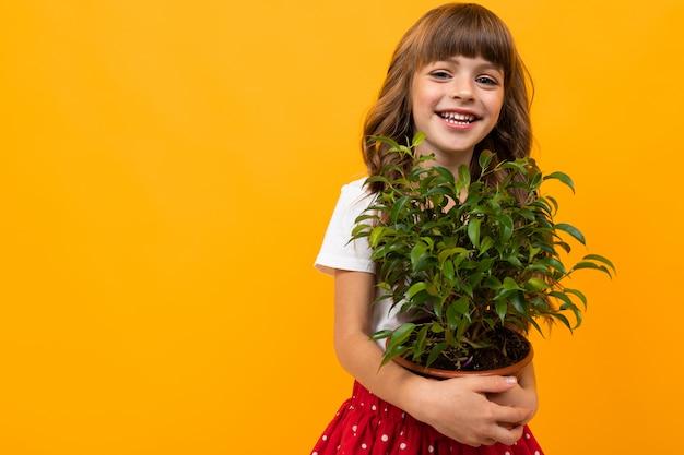 Niña sonriente con flor en maceta en naranja aislada