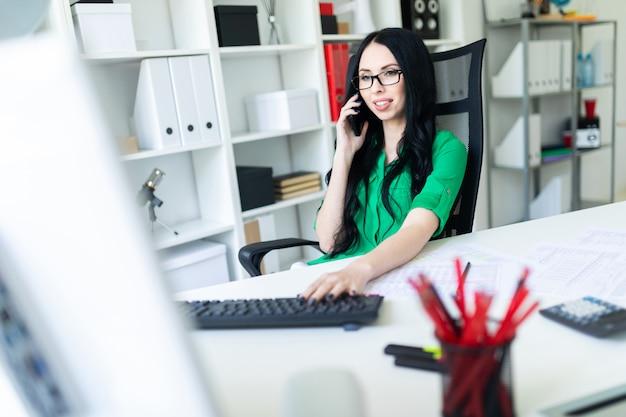 Niña sonriente con gafas en la oficina habla el teléfono y tiene una mano en el teclado.